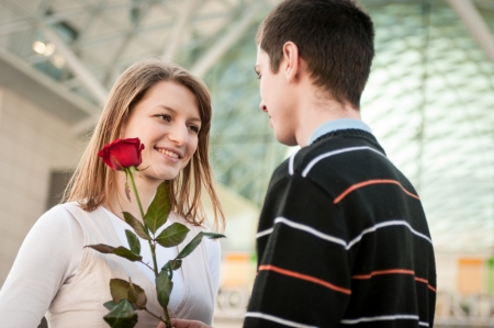 Young man handing over a flower (red rose) to woman - outdoor lifestyle scene photo