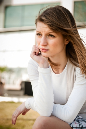 oudoor: Depression - portrait of young worried woman oudoor in urban environment
