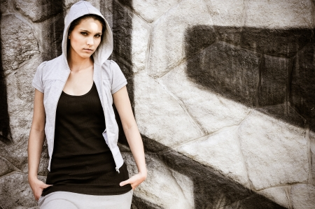 Young person (teenage girl) with hood in hip hop style standing at black and white graffity wall with copy space photo