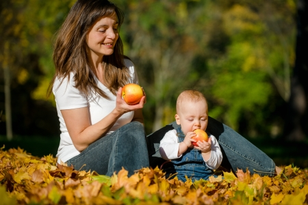 Beautiful baby with mother eating apples outdoor in nature photo