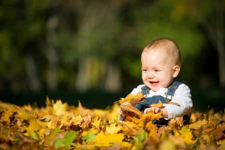 joy of life: Beautiful happy baby in autumn nature - sitting in leaves Stock Photo