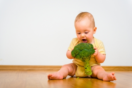 Baby eating broccoli indoors - healthy living Stock Photo
