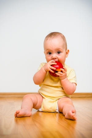 Baby eating apple lying on floor - healthy lifestyle photo