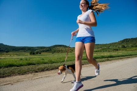 Beautiful teenage girl jogging with her pet (beagle dog) in nature photo