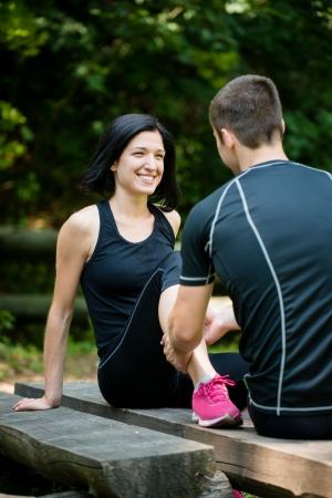 masaje deportivo: El hombre joven da masaje del becerro de la mujer sonriendo después de correr