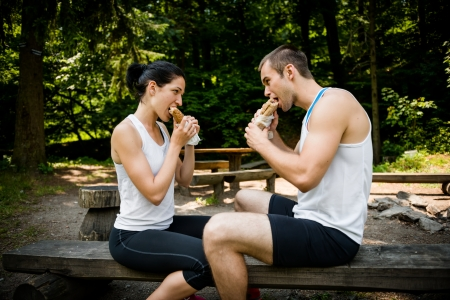 Young couple eating together after jogging outdoor in nature photo