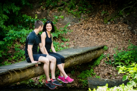 foot bridge: Young sport couple relaxing after sport training on foot bridge in nature