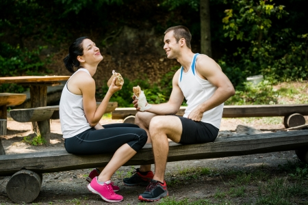 Young couple having fun while eating after sport training outdoor in nature photo