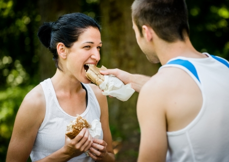 Young couple eating after sport training outdoor in nature - man feeds woman photo