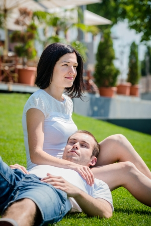 tenager: Young couple date - woman sitting on grass with his head laid on her tights