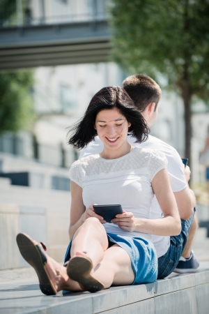 Young couple in street - man with smartphone, woman with tablet Stock Photo - 25087619