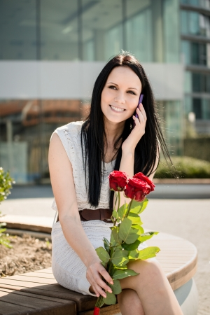 Young beautiful woman with red roses calling with mobile phone photo