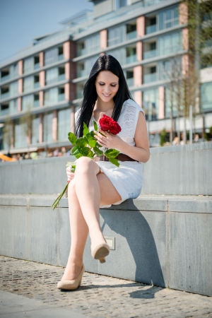 Young beautiful woman with red roses - outdoorf lifestyle portrait photo