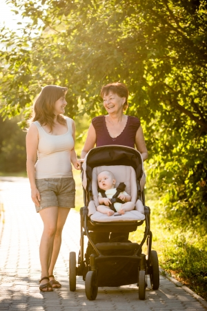 On a walk - grandmother with her daughter and her granddaughter in stroller photo