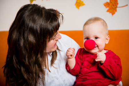 long nose: Mother playing with her smiling baby - child has red clown nose Stock Photo