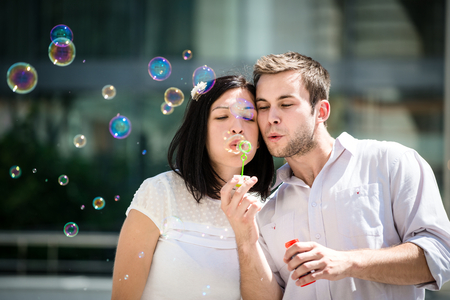 Young couple have great time together with bubble blower - outside in street photo