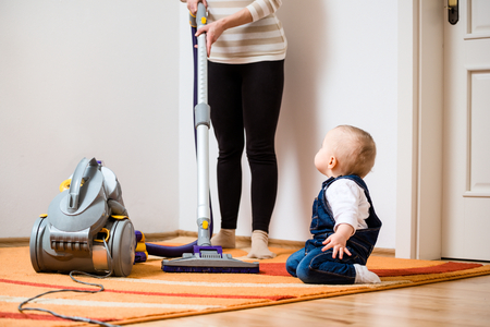 home keeping: Cleaning up the room together - mother and her baby  with vacuum cleaner