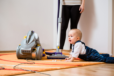 keeping room: Cleaning up the room - woman with vacuum cleaner, baby sitting on floor Stock Photo