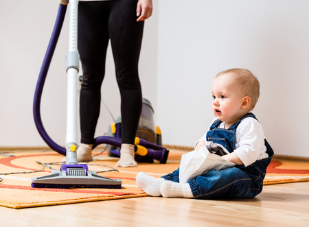 home keeping: Cleaning up the room - woman with vacuum cleaner, baby sitting on floor Stock Photo