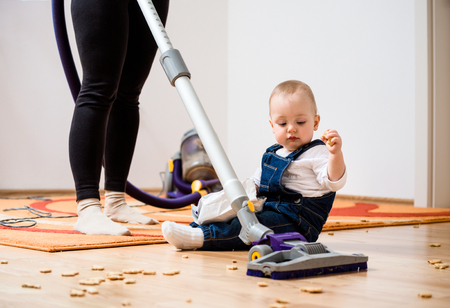 keeping room: Woman cleaning with vacuum cleaner, baby sitting on floor and biscuits all around Stock Photo