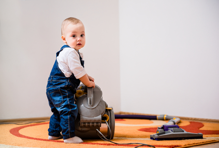 keeping room: Little baby standing at vacuum cleaner - home interior