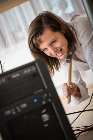 Furious young business woman having problem with computer - hammer in hand photo