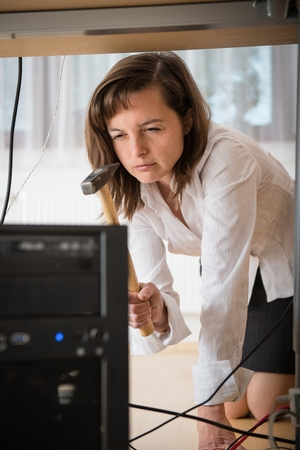 Young business woman having problem with computer and trying to recover it with hammer Stock Photo