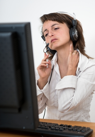 Young business person with neck pain working at computer photo