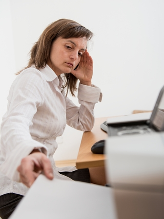 Business person in depression reaching hand and taking paper from printer on workplace photo