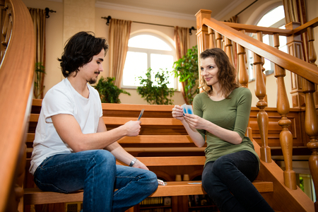 Young couple playing cards together in home - sitting on stairs photo