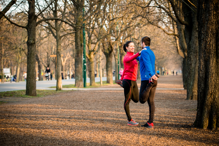 Young couple stretching muscles before jogging - outdoor in nature photo