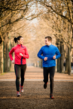 Young couple jogging together in tree alley - looking on each other photo