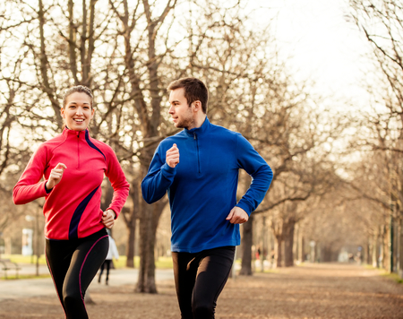 Young couple jogging together in tree alley - late autumn Stock Photo