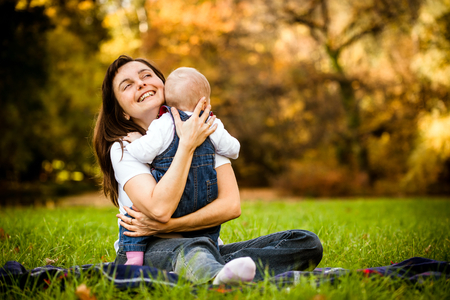 Happy mother holding her baby - sitting outdoor in nature photo