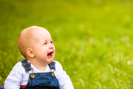 Babby sitting on grass and crying - outdoor with copy space