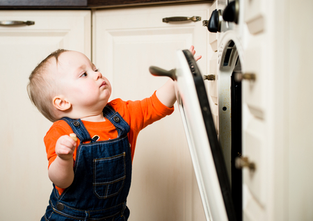 curious: Curious baby watching through glass of kitchen oven