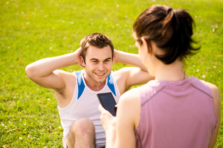 situps: Man making sit-ups while woman is watching time of exercise on mobile phone