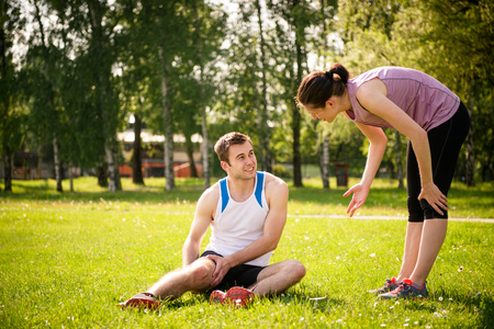 cramp: Woman is helping to young man with injured thigh from sport activity