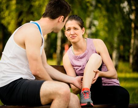 leg calf injury: Man helps to woman who injured her leg when jogging