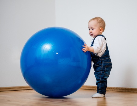 play room: Little baby is playing with big blue fit ball at home