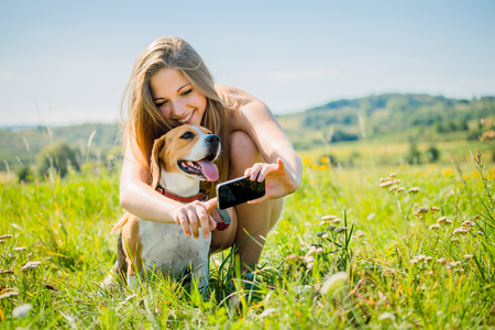 Young smiling woman showing something to her dog on smart-phone, outdoor in nature