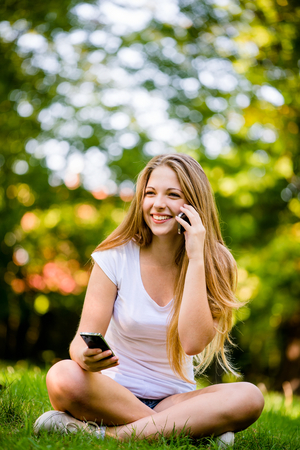 Teenage girl with 2 mobile phones - mobility and multitasking concept photo