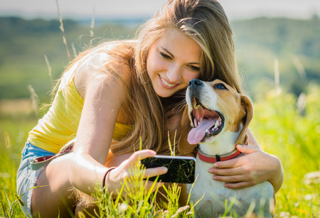 Teen girl taking photo of herself and her dog with mobile phone camera photo