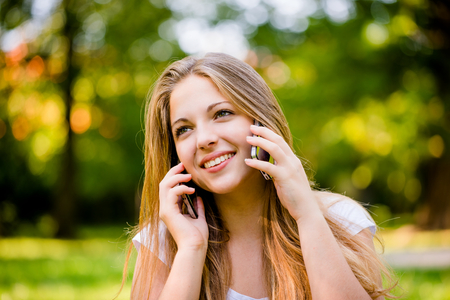 Teen girl calling with 2 mobile phones outdoor - mobility concept photo