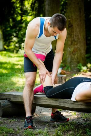 masaje deportivo: El hombre da masaje del becerro a su amigo después de entrenar el deporte al aire libre