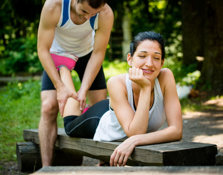 El hombre da masaje del becerro a su novia despu�s de entrenar el deporte - mujer encuentra en el banquillo photo