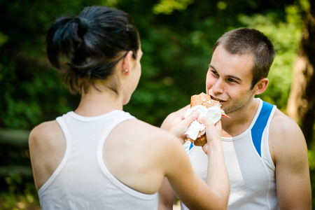 Young couple eating after sport training outdoor in nature - woman feeds man photo
