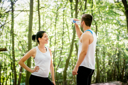 running water: Young couple relaxing after jogging in nature, man drinking water Stock Photo