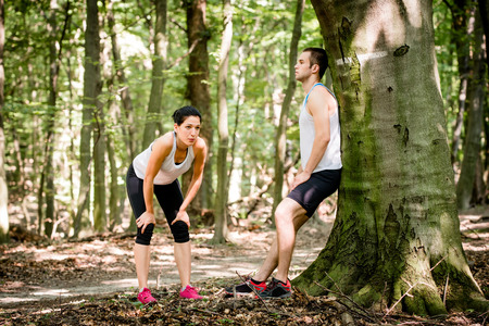 Young couple resting after jogging in nature, man leans against tree photo