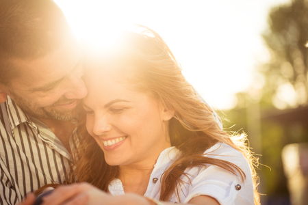 Happy couple having great time together - photographed at sunset against sun photo